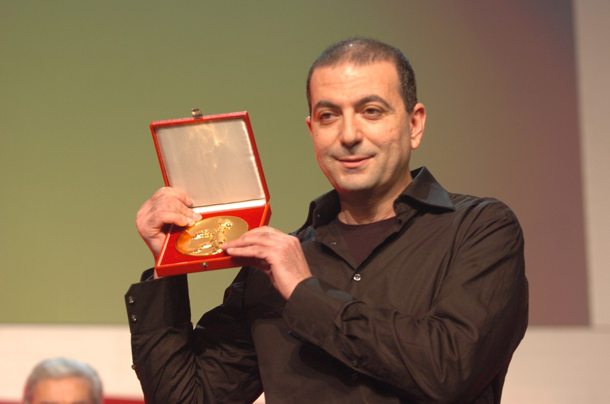 Hany Abu-Assad   Hany Abu-Assad with the Blue Angel award for  Paradise Now  for Best European Film, endowed with 25,000 Euros and donated by AGICOA.     Competition  –   Paradise Now   – Closing Gala – Prizes of the Independent Juries    Feb 19, 2005