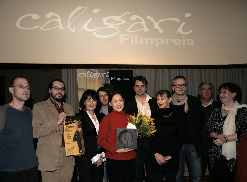 Caligari Filmpreis   Kanako Hayashi (Leiterin des Tokyo Filmex Festivals, die den Caligari Filmpreis für  Ai no mukidashi  stellvertretend entgegen nahm) inmitten der Juroren und Mitglieder des Bundesverbands kommunale Filmarbeit und dem Leiter des  Forums  Christoph Terhechte.     Forum  –   Ai no mukidashi  | Love Exposure     13. Februar 2009